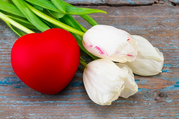 Colorful tulips and valentine's day hearts on wooden