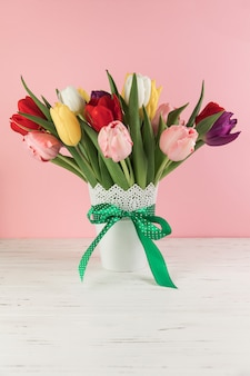 Colorful tulips vase with green bow on wooden desk against pink background