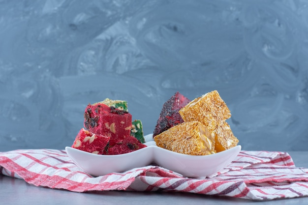 Красочные ароматы рахат-лукума на миске, на кухонном полотенце, на мраморном столе.