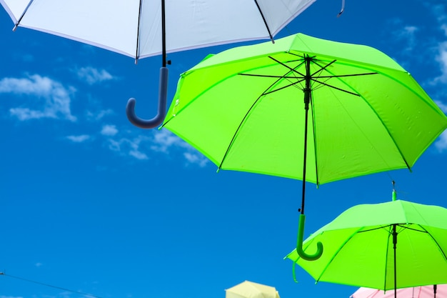 Colorful umbrella line decorate outdoor moving by wind on blue sky white cloud