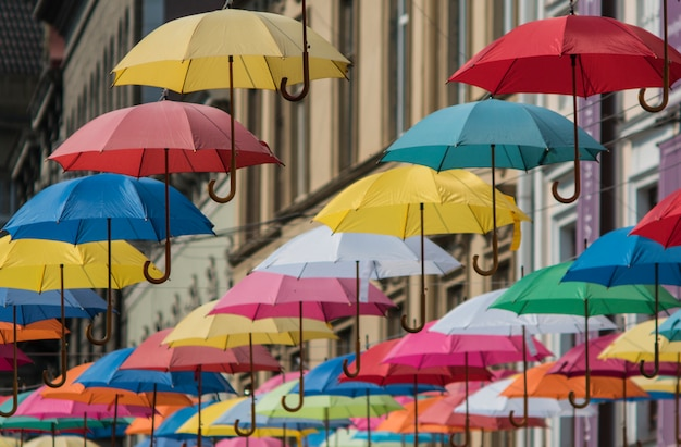 Colorful umbrellas hang on the background of the old city in the lviv
