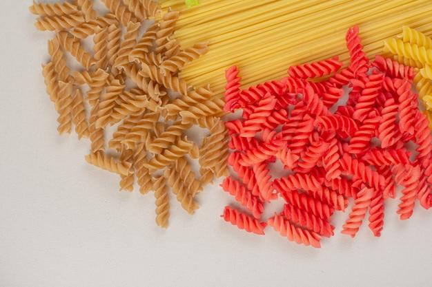 白い表面にカラフルな未調理のスパイラルパスタとスパゲッティ