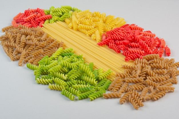 Pasta e spaghetti a spirale crudi variopinti sulla superficie bianca.