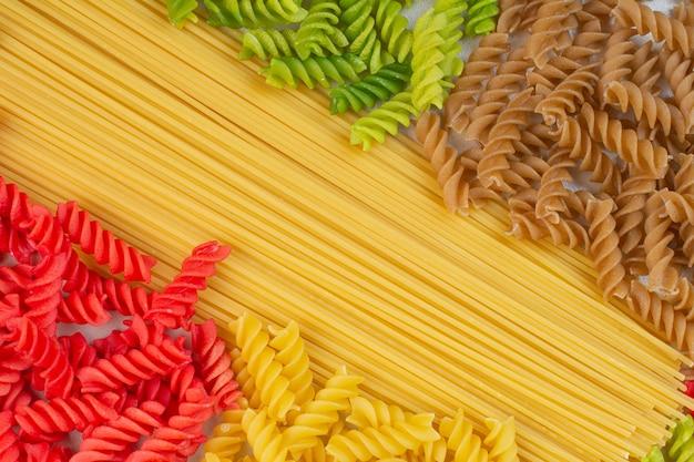 Pasta e spaghetti a spirale crudi variopinti sulla superficie bianca