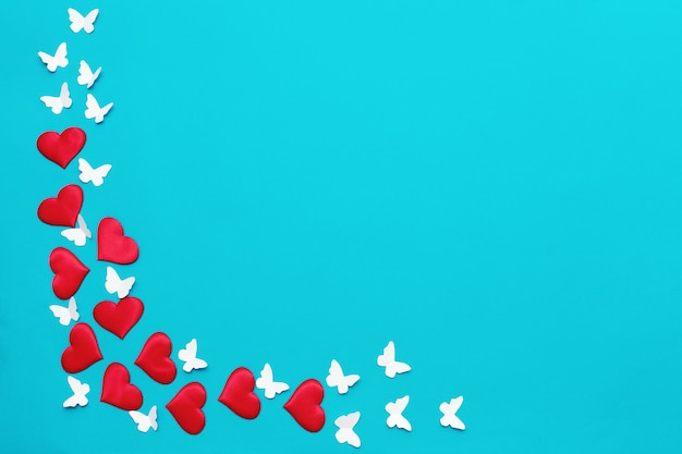 Colorful valentine background, greeting card made of red textile hearts and hand made white butterflies. love and valentine's day concept