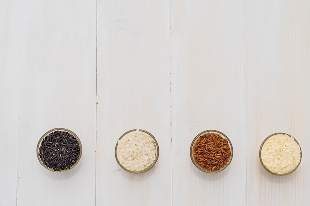 A colorful variety of rice in bowls arranged as a border over a wooden background