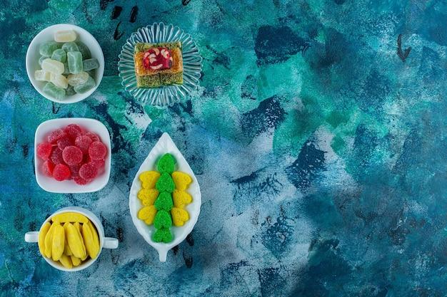 Красочный разнообразный десерт в мисках, на синем фоне.