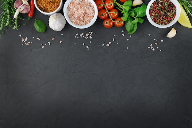 Colorful various herbs and spices for cooking on dark background, copy space, mock up.