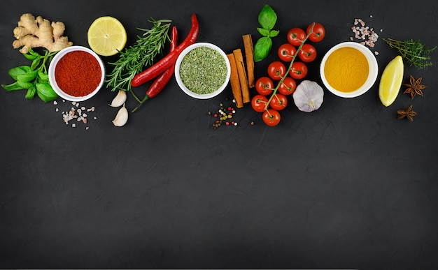 Colorful various herbs and spices for cooking on dark background.