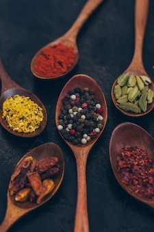 Colorful various spices in wooden spoons on old dark background. top view