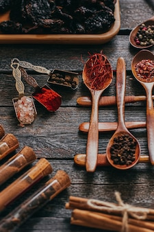 Colorful various spices in wooden spoons on old dark background.
