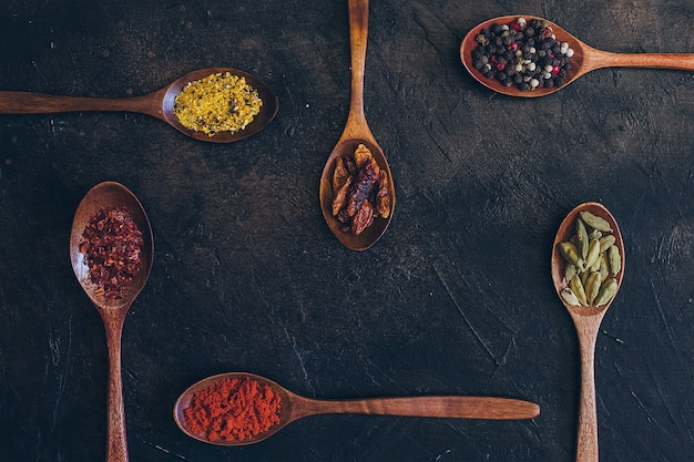 Colorful various spices in wooden spoons
