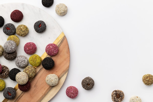 Colorful vegan candies energy balls on a plate on a white table
