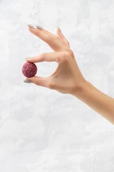灰色の女性の手にカラフルなビーガンキャンディーエネルギーボール
