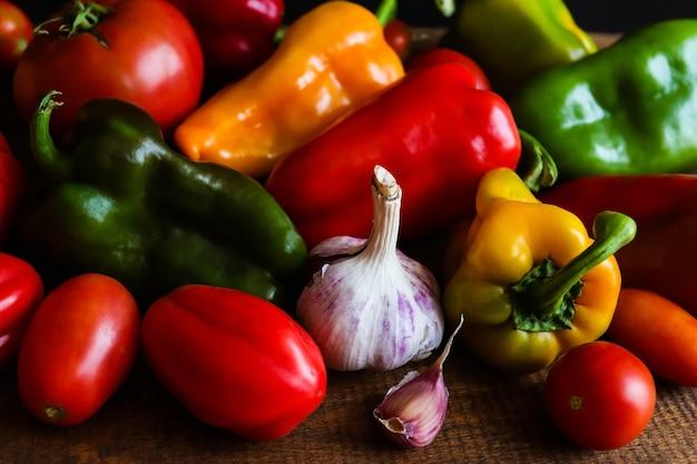 カラフルな野菜の背景木製のテーブルに新鮮な生のピーマントマトとニンニクを収穫します。