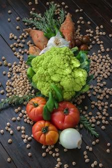 Colorful vegetables and chiskpeas dark background.