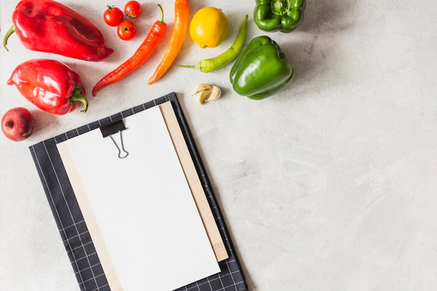 Colorful vegetables and clipboard with white paper on clipboard against white textured background