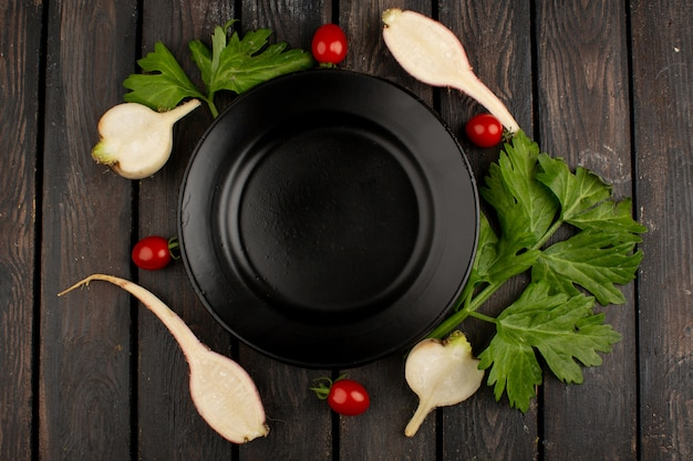 Colorful vegetables fresh ripe red cherry tomatoes and cut radishes with green leafs around black plate on a wooden rustic background