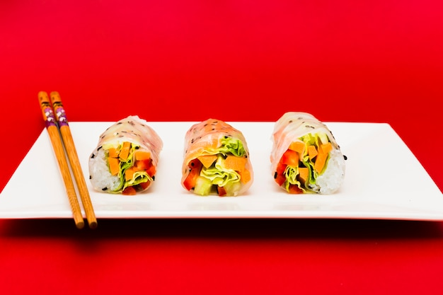 Colorful vegetables stuffed in rice spring rolls and chopsticks over white plate