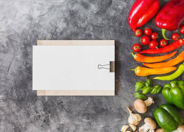 Colorful vegetables with blank paper on clipboard against grunge background