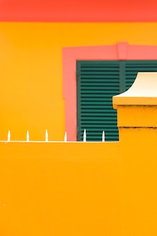 Colorful vintage building with green window shutters on the yellow wall