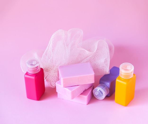 Colorful washcloth, plastic small travel bottles and bars of soap