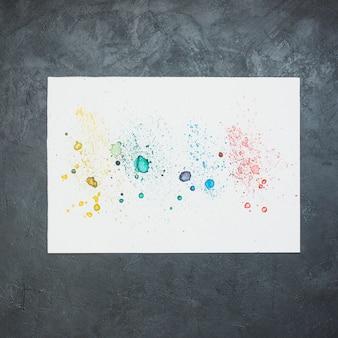 黒い背景に白い紙の上のカラフルな水の色の汚れ