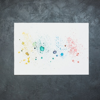 Colorful water color stain on white paper over black backdrop