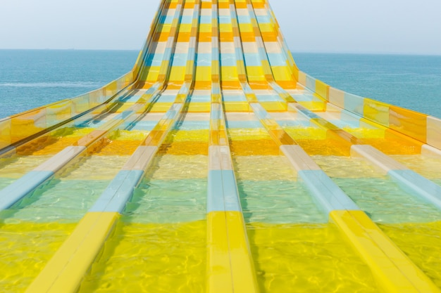 Colorful water feature slide at a resort or amusement park curving towards the camera with an ocean backdrop