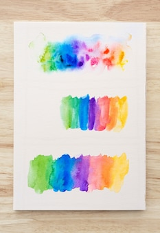Colorful watercolor brush strokes on white paper sheet with wood background. close-up.