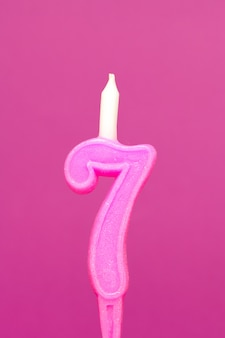 Colorful wax birthday candle  on pink background