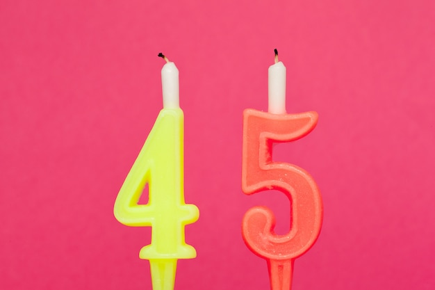 Colorful wax birthday candle  on pink