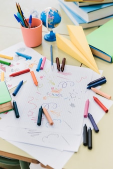 Colorful wax crayons scattered on desk with kid drawings