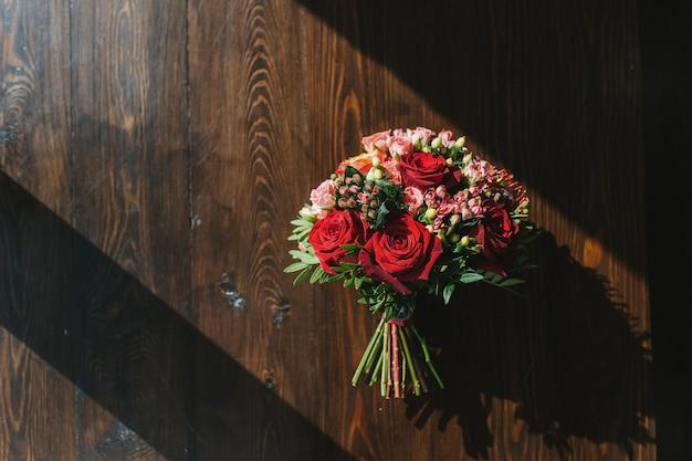 밝은 태양 빨간색과 분홍색 장미의 광선에 어두운 나무로 만든 테이블에 화려한 웨딩 부케