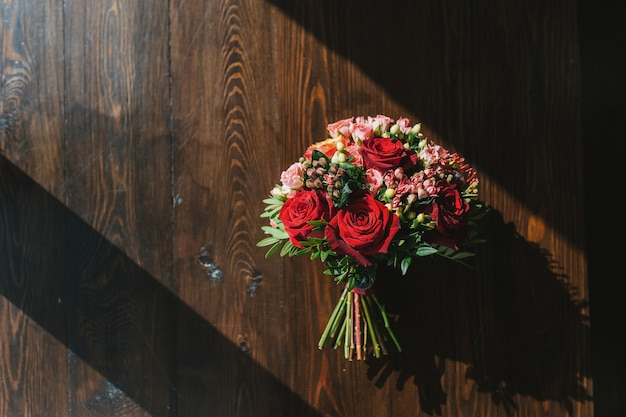 Colorful wedding bouquet on table made of dark wood in rays of bright sun red and pink roses