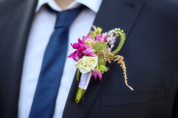 Colorful wedding boutonniere on suit of groom
