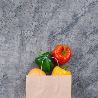 Colorful whole capsicum from the paper bag on concrete backdrop