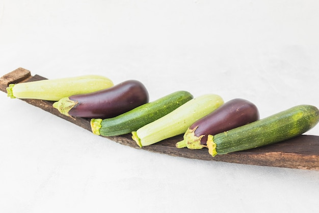 Colorful whole harvested eggplants on wooden tray against white background