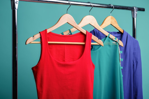 Colorful women's shirts on wood hangers on bluend. rgb