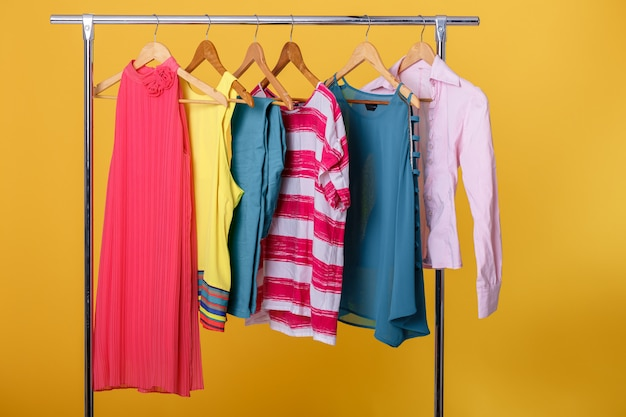 Colorful womens clothes on hangers on rack on orange.