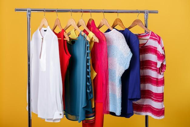 Красочные женские одежды на вешалках на стойке на оранжевый.