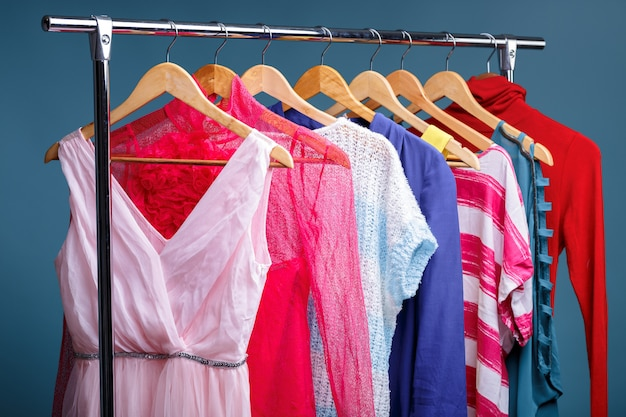 Colorful womens clothes on wood hangers on rack on blue