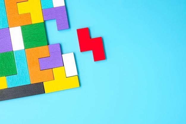 파란색 배경, 기하학적 모양 블록에 다채로운 나무 퍼즐 조각. 논리적 사고, 수수께끼, 솔루션, 합리적, 전략, 세계 논리의 날 및 교육의 개념