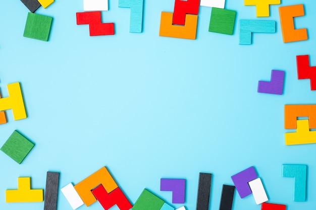 파란색 배경에 다채로운 나무 퍼즐 조각, 복사 공간이 있는 기하학적 모양 블록. 논리적 사고, 수수께끼, 솔루션, 합리적, 전략, 세계 논리의 날 및 교육의 개념