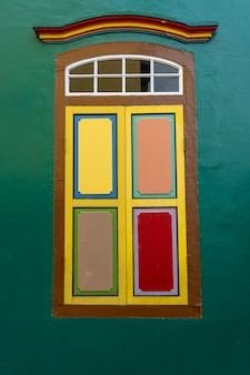 Colorful wooden abstract window, close up .colonial style architecture building in little india , singapore city . background and texture of bright architecture