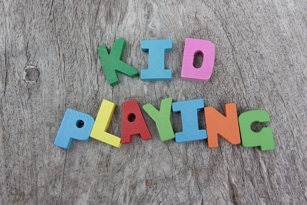 Colorful wooden alphabet blocks with wording kid playing on wooden floor