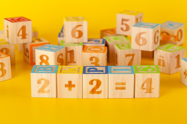 Colorful wooden blocks with letters on a yellow color