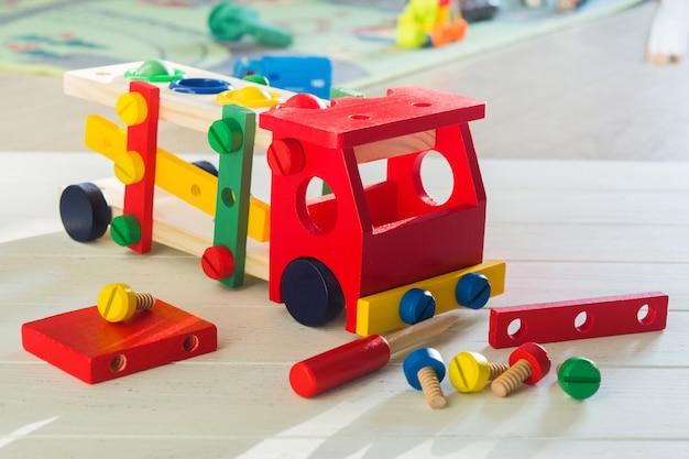 어린이를위한 다채로운 나무 자동차 생성자. 많은 세부 사항, 드라이버 및 나무 테이블에 나사와 유치원 교육 개념