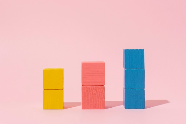 Colorful wooden cubes with pink background