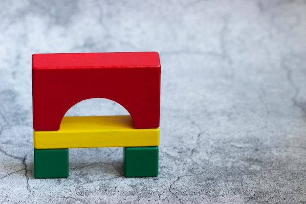 Colorful wooden details of the constructor on a gray background. selective focus.